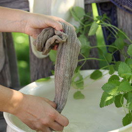 Die Nassen Leinenstrümpfe werden in kaltes Wasser getaucht und ausgedrückt