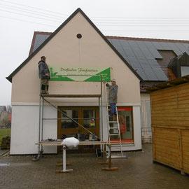 Das Dorfladenschild wird montiert.