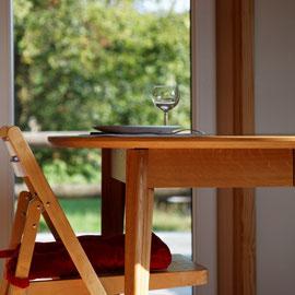 Le bout des bois - table au salon - vue sur la terrasse  et les champs