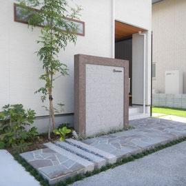 床に敷いてあるのは『鉄平石の乱形』です。御影石の延べ石を3本ポイントに入れました。植栽の緑が石の硬さを和らげてくれます。                                        岡山市南区T様邸 エクステリア フラワーチルドレン