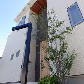屋根まで伸びた建物のニッチに合わせて選んだポールタイプの表札。名前、インターフォン、照明、ポストが付けられます。今回は特注で愛犬用のリードフックを付けました。                                                                 岡山市中区 S様邸 エクステリア フラワーチルドレン