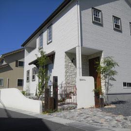全景。玄関周りの石貼り壁が特徴的な『ナチュラル+シンプル』な住宅です。エクステリアも住宅の雰囲気に合わせてデザインしています。                                             岡山市北区U様邸 エクステリア フラワーチルドレン