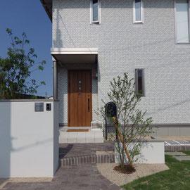 特に気を配ったのは、建物と外構の素材感のバランスです。ポイントとなるステンレス製の表札やネイビーブルー色のポストは施主様が丁寧に選ばれました。土で残してある部分は草花を植えられるご予定です。                                                                                                                         岡山市北区 F様邸 エクステリア フラワーチルドレン