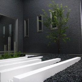 長さの違う5本の直線ラインはポリウレタン樹脂塗料で仕上げています。光沢のある仕上げりがデザイン性を高めてます。植栽はハイノキ株立ち(右奥)と低木のコクチナシ(左奥)です。  岡山市北区Y様邸 ガーデン フラワーチルドレン