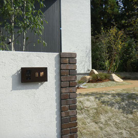 門塀はシンプルを心がけましたが、ポイントで深い色合いのレンガ角柱を使い存在感を出しています。レンガの角を塗装壁より出すことにより影ができ、素材感が引き立ちます。                                                                      岡山市中区Y様邸 エクステリア フラワーチルドレン