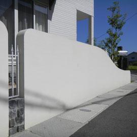 道路境界の塗装壁にはポイントでアルミ鋳物のフェンスを挟み込みました。フェンスの下にも、アプローチやテラスで使われている耐火レンガを使用しています。                                                            岡山市北区U様邸 エクステリア フラワーチルドレン