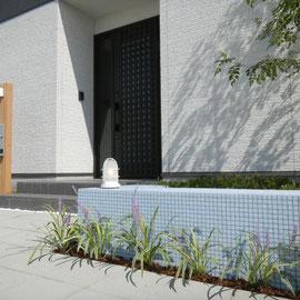 無難なデザインの中にも遊び心は必要です。ガラスのモザイクタイルを貼ったベンチは座ったり、花台や荷物置き場になったりと実用も兼ねています。                      岡山市南区 エクステリアリフォーム フラワーチルドレン