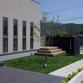 玄関前のタイル貼りスペースも庭の一部に取り込まれるデザインです。芝生は人工芝を採用しています。 岡山市北区Y様邸 フラワーチルドレン。