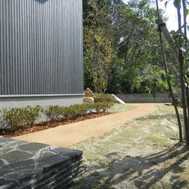植物に挟まれたナチュラルな園路は、「自然素材だけを使っているエコ商品」ということで採用された『透水性自然土固化防草材』です。                                                                                  岡山市中区Y様邸 エクステリア フラワーチルドレン