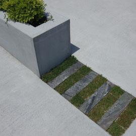 植栽の花壇もスロープの低い壁もコンクリートブロックのモルタル仕上げです。あえて塗装をしないことにより、経年変化による汚れを気にせずに使えます。スロープ床面はコンクリートのハケ引き仕上げです。滑りにくくなり、タイヤの跡も付きづらくなりますので、スロープ部分にはおすすめの仕上げ方です。                                                                                       倉敷市二日市 T様邸 エクステリア フラワーチルドレン