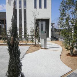 メインアプローチは曲線で、木々の間を抜けていくようにデザインしました。直線ラインが多い中でのポイントで使う曲線は効果的です。舗装材は白い玉砂利の洗い出し仕上げを使い、駐車スペースより質感を上げています。  倉敷市 I 様邸 エクステリア フラワーチルドレン