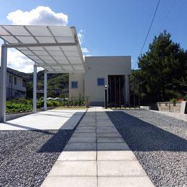建築のデザインを邪魔しないように、素材もライン(直線)もシンプルにしています。アプローチのコンクリート平板は、以前この土地にあったご家族の工場の床に使われていた物をリユースしました。                                                                                                                                          岡山市南区 S様邸 エクステリア フラワーチルドレン