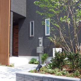 シンボルツリーが植えられている花壇は化粧ブロックとコンクリート製の笠木で作成。建物に合わせた色使いで引き締まって見える色と質感を選びました。                                                         岡山市南区 J様邸 フラワーチルドレン