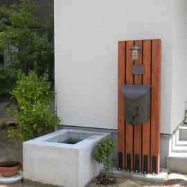 天然木を並べて作ったオリジナル機能門柱です。天然木を自然乾燥させた材料ですので、歪みは無いですが、割れは多少出ています。その割れが味わいになっています。木の足元は金具で止めて地面に付かないようにしています。  岡山市北区S様邸 エクステリア フラワーチルドレン