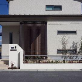 門塀は玄関ドア前の縦格子パーティションを引き立てるように抑えたデザインにしました。坪庭を囲う塀は下屋の水平ライン、横長窓が綺麗に見えるようにシンプルな横ラインのフェンスを選びました。                                                                                                                 倉敷市茶屋町早沖 N様邸 エクステリア フラワーチルドレン