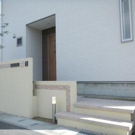 家がT字路の突き当りにあるので玄関の目隠しを兼ねてファサードのポイントにもなる門塀を作りました。高さの違う壁を前後にずらしモザイクタイルをラインで入れています。                                                           岡山市南区S様邸 エクステリア フラワーチルドレン