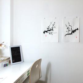 zwei ungerahmte Pflaumenblütenzweige an einem Schreibtisch