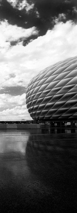 Die Allianz Arena in München als vertikales Panorama-Foto in Schwarzweiß
