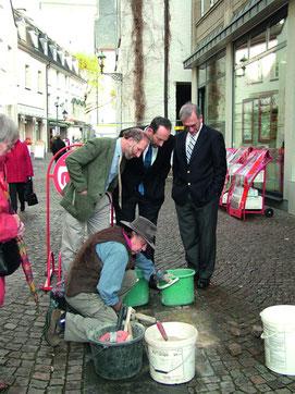 Vier Männer bei einer Stolperstein-Verlegung