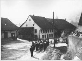 Kirchbachstrasse: Noch fliesst der Bach offen der Kirchhofmauer entlang (ca. 1955?, Pozession an einem Weissen Sonntag)