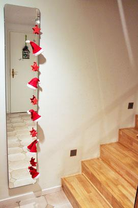 Girlande in rot - weiß mit Weihnachtsmann Mützen.