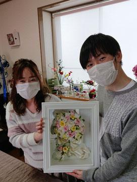 生花からプリザーブドフラワーに加工したフレーム作品を持つカップル