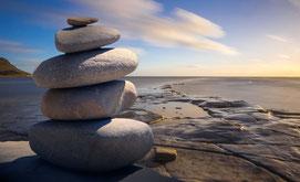 Vier aufeinanderliegenden Steine vor dem Meer