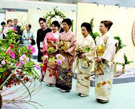 さまざまな生け花をご覧になる久子さま(写真右から3人目)と絢子さま(写真右から4人目)=12日午後、沖縄コンベンションセンター