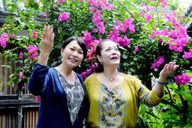 うりずんの季節を迎え鮮やかなブーゲンビレアの前で歌う来間高子さん(右)と金城弘美さん(左)=石垣市新川