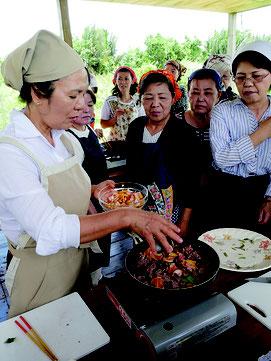 月桃フラワーをフライパンに入れ、牛肉の香り炒めを作っている様子。左は講師の嵩西洋子さん=10日昼、石垣島胡椒園