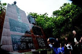 忘勿石之碑前で慰霊祭が執り行われた=15日、南風見田浜