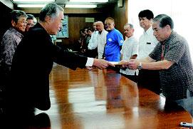 中山市長に対し、早期の配備容認表明を求める要請書を提出する三木会長(左)。漢那副市長が受け取った=11月2日、市役所