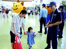海保職員からチラシを受け取る観光客=2日午前、離島ターミナル