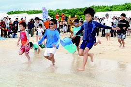 テープカット後、子どもたちが一斉に海へと飛び込んだ=21日午前、マエサトビーチ