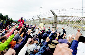 大会終了後、基地に向かって「基地は要らない」と拳を振り上げる参加者=25日、米軍キャンプ・シュワブ前