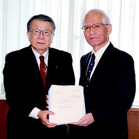答申を手交する安里会長(写真左)と受け取る浦崎副知事=26日、県庁