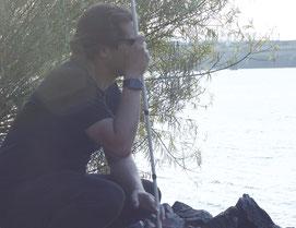 Erdin hockt auf Steinen, mit dem Blick zum Elbwasser und den Blindenstock in der linken Hand haltend.