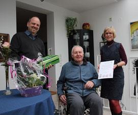 Michael Weidenfeller und Ingrid Dahl überbringen Wolfgang Strinz die Glückwünsche des Vereins.