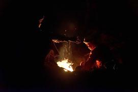 Beduinen sitzen am Feuer und backen Brot