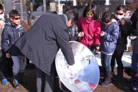 集光型のソーラークッカーを体験する子どもたち