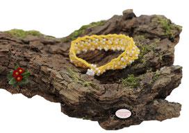 bracelet Aerin, réalisé au crochet d'art, un bijou textile réalisé en coton jaune, des perles blanches ont été incluses en cours de travail. Un bijou hypoallergénique, il se ferme par une boule de perles glissée dans un maillon crocheté et perlé