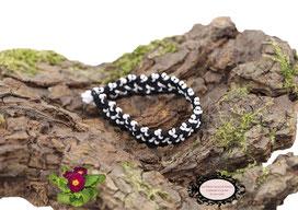 bracelet Aerin, réalisé au crochet d'art, un bijou textile réalisé en coton noir, des perles blanches ont été incluses en cours de travail. Un bijou hypoallergénique, il se ferme par une boule de perles glissée dans un maillon crocheté et perlé