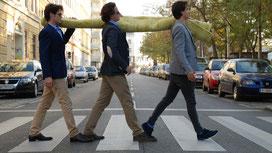 Drei Männer tragen Teppich über die Straße
