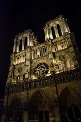 Notre Dame bei Nacht kannst du u. a. im Rahmen einer Seinerundfahrt betrachten. Vor dem Kirchenportal tummeln sich allerhand Gaukler, Künstler und Maler