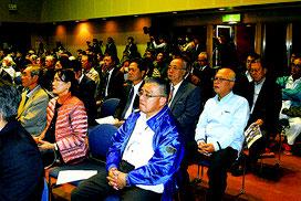 尖閣諸島開拓の日式典に参加し、登壇者のあいさつを聞く人たち=14日午後、市民会館大ホール