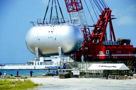 新タンクが石垣港に届き、移送と設置作業が行われた=1日、新港地区