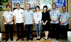 浦崎副知事と高尾氏(中央)らで記念撮影=25日、県庁
