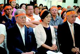 沖縄市長選で落選が決まり、厳しい表情を見せる諸見里氏(中央)ら=22日午後10時過ぎ、選対本部