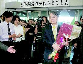 知事として8年間の任期を終え、職員らに見送られ、花束を手に沖縄県庁を後にする稲嶺恵一氏=2006年12月(共同)