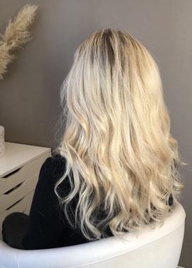 Cette photo représente une femme blonde de dos qui vient de recevoir un pose d'extensions de cheveux naturelles blondes.